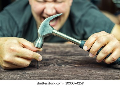 Male worker blowing a hammer on the finger