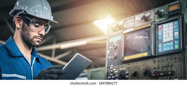 Male worker in blue jumpsuit and white hardhat inspecting the machine with tablet device.