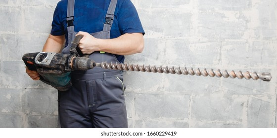 Male worker builder holds big drill background gray wall.