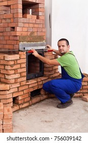 Male worker building a masonry heater- fitting a metallic door into the structure
