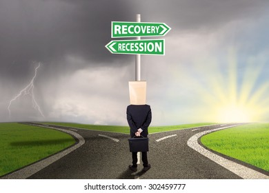 Male worker with cardboard head looking at signboard with recovery recession words on the road