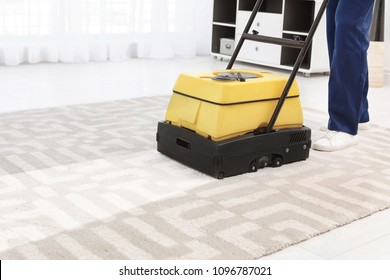 Male worker with carpet cleaner indoors, closeup