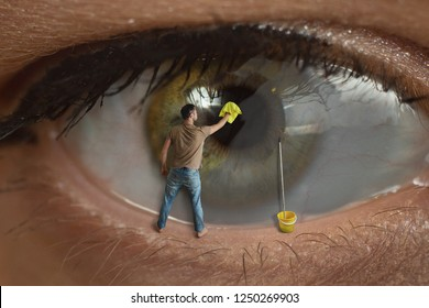 Male worker cleaning the surface of the pupil of the eye with a rag. Concept of healthy eyesight, conjunctivitis and window cleaning