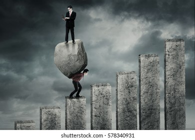 Male worker climbing a chart and carrying a big boulder while his partner using laptop on the boulder