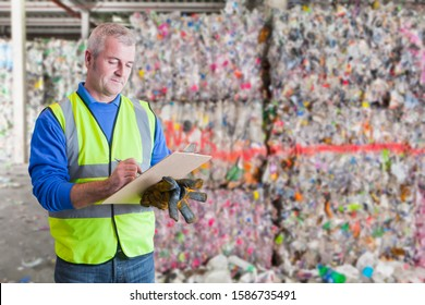 Male Worker With Clipboard Checking Waste Recycling Bales
