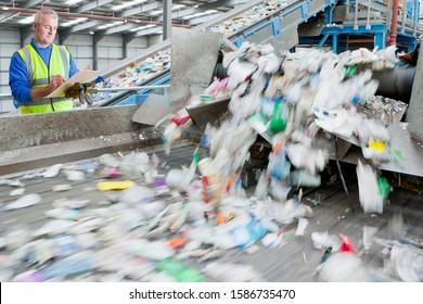 Male Worker With Clipboard In Waste Recycling Plant