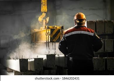 Ein männlicher Arbeiter kontrolliert den Produktionsprozess in einer Fabrik, da ein Kranich ein Stahlbetonprodukt mit Löchern bewegt. Verstärkte Betonsäulen mit Metallhaken und -ketten