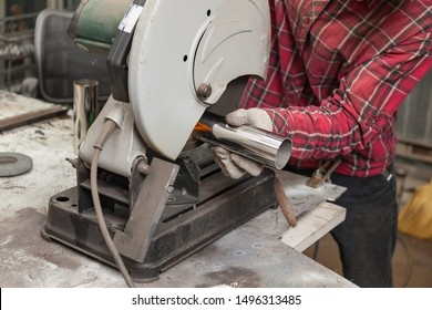 A male worker cuts a stainless steel pipe on a special machine for vertical sawing of metal parts for industrial use. Making exhaust for a car.