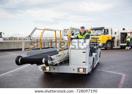 Male Worker Driving Luggage Conveyor Truck On Airport Runway
