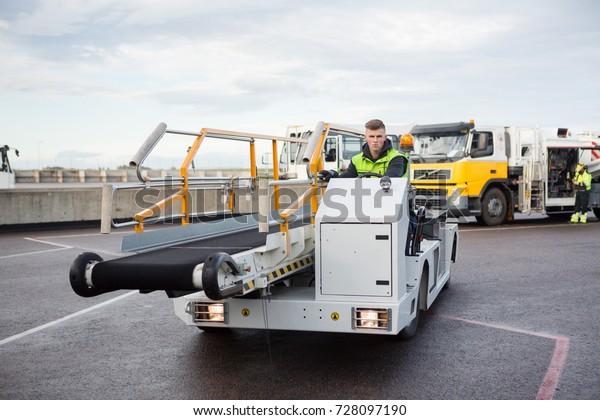 Male Worker Driving Luggage Conveyor Truck On Airport Runway