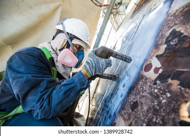Male worker earing a mask test steel tank butt weld carbon background white contrast of magnetic field test