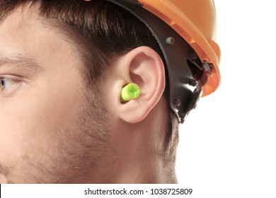 Male worker with earplug on white background. Hearing protection equipment