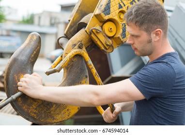 Male worker fastening mobile crane hook.