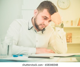 Male worker is having complicated issue with project in office.