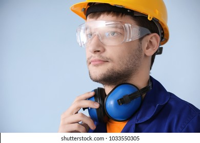 Male worker with headphones on grey background. Hearing protection equipment