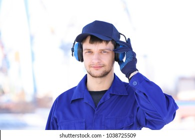 Male worker with headphones outdoors. Hearing protection equipment