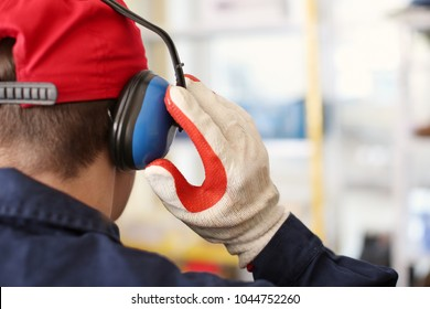 Male worker with hearing protectors, indoors