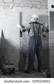Male worker in helmet is measuring wall with level.