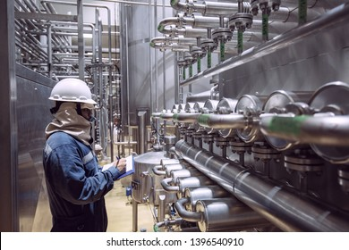 Male worker inspection the process of food drink at the manufacturing pipeline and stainless tank