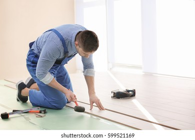 Male worker installing laminate flooring