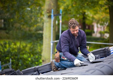 Male worker laying tiles on the roof while roofing a house near the city of Breda, Netherlands, Europe, in a traditional craftsman way