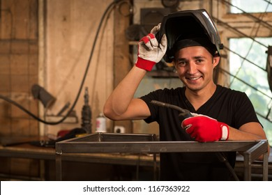 Male worker leaning on metal frame with welder in hand, lifted special protective mask with other hand over face. Man wearing in black t shirt and protective gloves smiling and looking at camera.