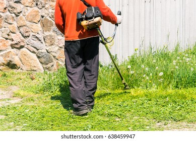 A male worker on the plot is putting the grass around the house in order. Mowing grass by hand lawn mower.