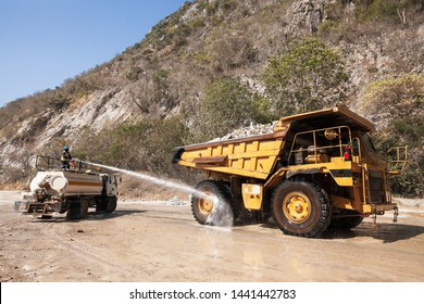 Male worker on water truck is spraying water on the large wheel truck in cement mining, limestone mountain in the background.