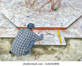 Male worker is paving the floor with marble slabs, high angle view with copy space