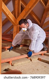 Male worker placing a rock wool thermal insulating panel between and under the scaffolding of the floor in the attic space