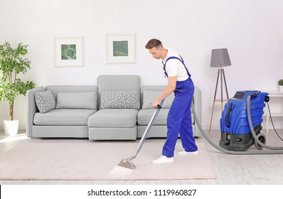 Male worker removing dirt from carpet with professional vacuum cleaner indoors