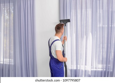 Male worker removing dust from curtains with professional vacuum cleaner indoors