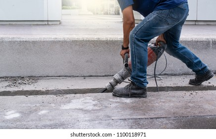 Male worker repairing driveway surface with jackhammer, digging and drilling concrete roads