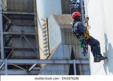 Male worker rope access height safety inspection of thickness storage oil and gas tank industry