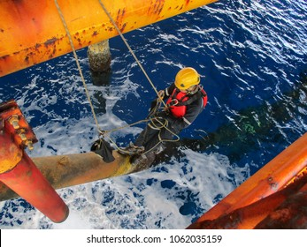 Male worker rope access  inspection of thickness offshore drill yellow oil and gas production petroleum pipeline.