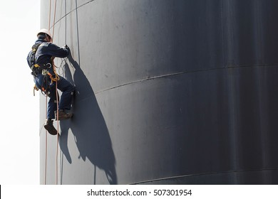 Male worker rope access  inspection of thickness storage tank industry.