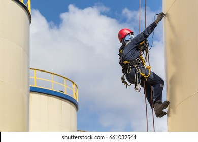 Male worker rope access  inspection of  thickness shell plate storage tank oil industry and blue sky.