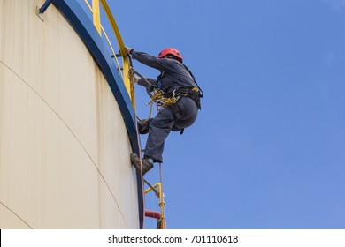 Male worker rope access  inspection of  storage tank oil industry.