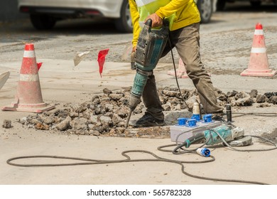 Male worker with safety equipment drilling concrete repairing driveway surface with jackhammer ,danger sign concept. Professional worker.