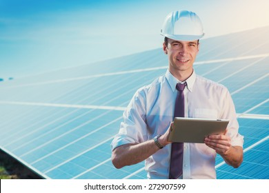 Male worker solar power plant with a tablet on a background of photovoltaic panels.