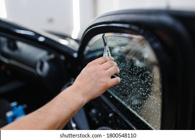 Male worker with squeegee wipes car tinting