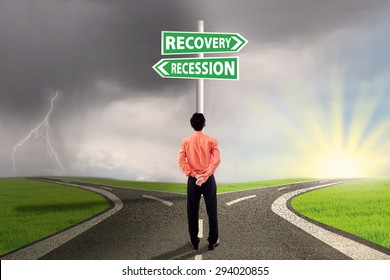Male worker standing on the road and look at a signpost with two choice to recovery or recession finance