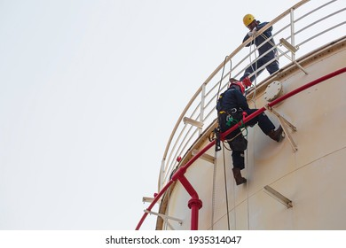 Male worker standing pipe rope access industrial working at height tank oil wearing harness, helmet safety equipment rope access inspection of thickness tank oil and gas.
