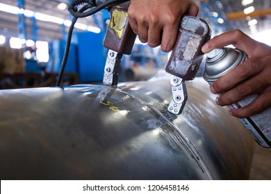 Male worker test steel pipeline butt weld carbon background white contrast of magnetic field test