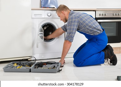 Male Worker With Toolbox Repairing Washing Machine In Kitchen