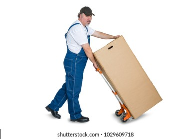Male worker transporting large cardboard box with trolley against white background