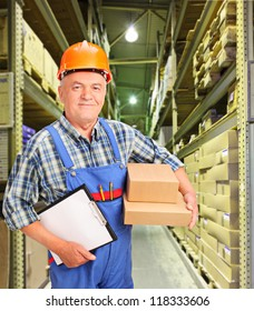 A male worker in uniform holding boxes and clipboard at warehouse