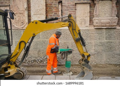 male Worker in uniform use vibratory plate compactor for path construction. Plate compactor for compaction soil or pavement or sidewalk. Indastrial equipment. Laying and tamping paving slabs.