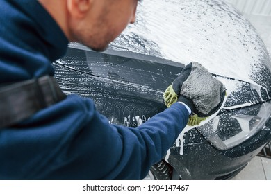 Male worker in uniform washing new modern car that is full of soap. Conception of service.