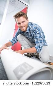 a male worker unrolling carpet